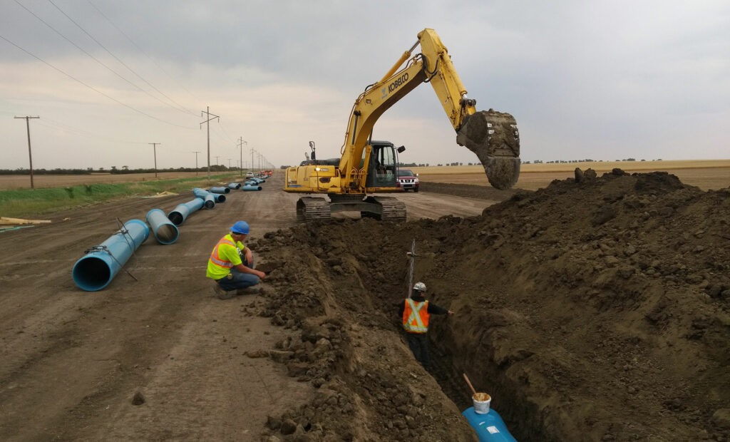 Two workers Trenching for Western Water Management